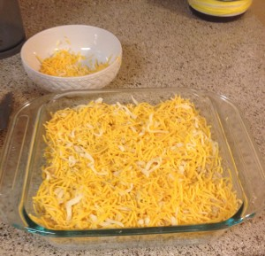 Top with shredded cheddar cheese.  Give it a little shake to let the cheese get in between the tots.  Yummy cheesy potatoy goodness!