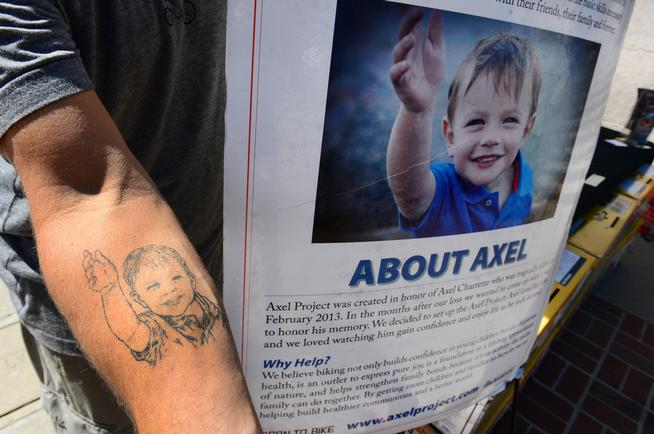 Randy Charrette shows off the tattoo of his son that he has on his right forearm next to his booth The Axel Project at Civic Center in Denver, August 24, 2014. (Helen H. Richardson, The Denver Post)