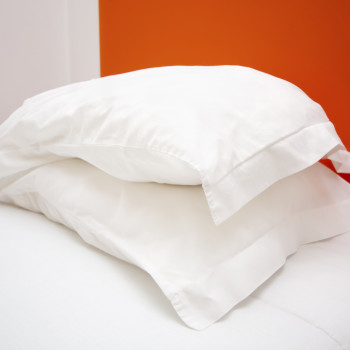 Twin-bed-and-shams-behind-orange-wall-iStock_000043879866Medium-350x350